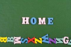 HEM- ord på grön bakgrund som komponeras från träbokstäver för färgrikt abc-alfabetkvarter, kopieringsutrymme för annonstext lära Arkivfoto