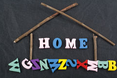 HEM- ord på svart brädebakgrund som komponeras från träbokstäver för färgrikt abc-alfabetkvarter, kopieringsutrymme för annonstex Arkivfoton