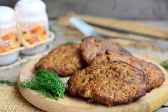 Hem- pannkakor för feg lever med grönsaker på ett wood bräde Pannkakor för stekt kycklinglever med moroten och löken Matlagningle arkivfoto