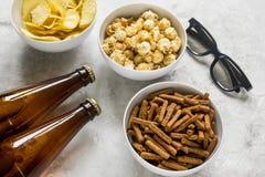 Hem- parti med TVatt hålla ögonen på, mellanmål och öl på stenbakgrund Arkivfoto