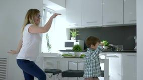 Hem- parti, mum med ungen som dansar glatt i lägenhet i kök stock video