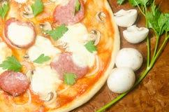 Hem- pizza med salami- och mozzarellaost med champinjoner och Royaltyfri Fotografi