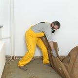 Hem- renovering, gammal matta tar bort Arkivbild