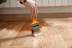 Hem- renoveringparkett Lacka målarpenselslaglängder på en träparkett royaltyfri foto