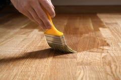 Hem- renoveringparkett Lacka målarpenselslaglängder på en träparkett arkivfoto