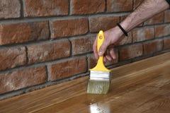 Hem- renoveringparkett Lacka målarpenselslaglängder på en träparkett fotografering för bildbyråer
