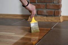 Hem- renoveringparkett Lacka målarpenselslaglängder på en träparkett royaltyfri bild