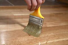 Hem- renoveringparkett Lacka målarpenselslaglängder på en träparkett arkivbild