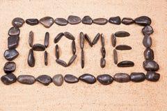 Hem- skriftligt för ord med kiselstenar på sanden Arkivbilder