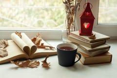 Hem- stilleben för slags tvåsittssoffa: ljusstake och böcker på fönsterbräda mot landskap utanför Höstferier, läs- tidbegrepp arkivbilder