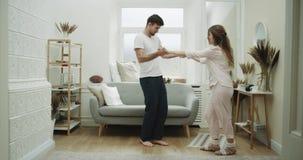 Hem- stilpar som fantastiskt spenderar en tid tillsammans i vardagsrummet som tillsammans dacing, i pyjamas stock video