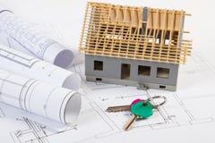 Hem- tangenter, litet hus under konstruktion och elektriska teckningar, byggande hem- begrepp Arkivfoto