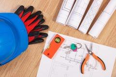 Hem- tangenter med elektriska teckningar, den skyddande hjälmen med handskar och orange arbetshjälpmedel, begrepp av byggnadshemm Arkivfoto