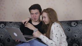 Hem-, teknologi- och förhållandebegrepp - stiligt par med bärbar datordatoren hemma lager videofilmer