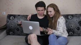 Hem-, teknologi- och förhållandebegrepp - stiligt par med bärbar datordatoren hemma stock video