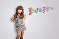 Hem-, teknologi- och musikbegrepp - liten flicka med hörlurar Arkivfoto