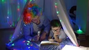 Hem- tid lyckligt barn med farsan in i den roliga perukläseboken i ljus av ficklampan som ligger på det magiska tältet med girlan arkivfilmer