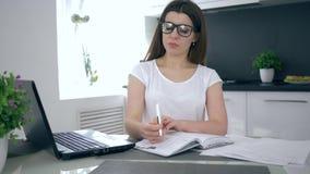 Hem- utbildning, den kvinnliga studenten i exponeringsglas tar anmärkningar i anteckningsbok stock video