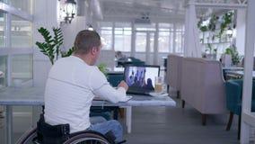 Hem- utbildning, den pensionär lamslog mannen i hjulstol skriver anmärkningar i anteckningsbok, medan hålla ögonen på online-utbi lager videofilmer