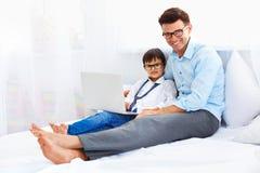 Hem- utbildning Fader och son som ler och ser kameran Royaltyfria Bilder