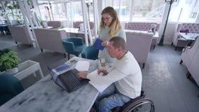 Hem- utbildning, lyckad rörelsehindrad man i rullstol med kvinnlig användande modern datateknik för lärare under stock video