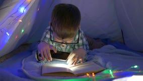 Hem- utbildning, pojke med exponeringsglas rymmer en mobiltelefon med ficklampan i hans händer och är läseboken i tält stock video