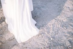 Hem of white dress, space for text. Sand and dress royalty free stock photo