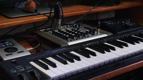 Hem- workspace för musikinspelningstudio med det blandande brädesoundboard och tangentbordet Vändande knoppar för solid tekniker  lager videofilmer