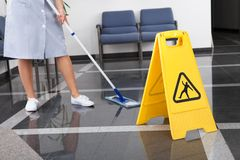 Hembiträde Cleaning The Floor royaltyfria bilder
