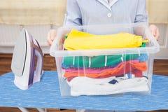 Hembiträde Holding Laundry Basket Arkivbilder