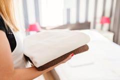 Hembiträde som kommer med nya rena handdukar till rummet Fotografering för Bildbyråer