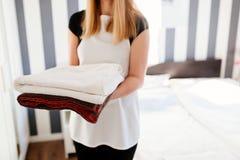 Hembiträde som kommer med nya rena handdukar till rummet Arkivfoton