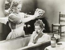 Hembiträde som pressar svampen på kvinna i badkar Arkivbild