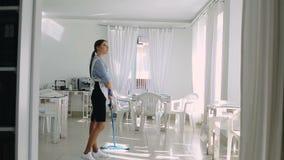 Hembiträdet som tvättar golvet lager videofilmer