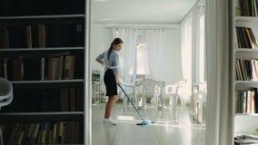 Hembiträdet som tvättar golvet arkivfilmer