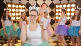 Hembra adolescente atractiva con el baile feliz del pelo rubio en celebración de días festivos de la noche de la muchacha s hacia metrajes