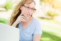 Hembra adolescente con los vidrios al aire libre usando su ordenador portátil Foto de archivo libre de regalías