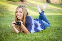 Hembra adolescente que manda un SMS en su teléfono celular al aire libre Foto de archivo libre de regalías