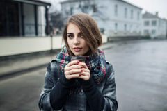 Hembra adulta joven con la taza de café de papel que permanece en la calle de la ciudad en día lluvioso nublado; Imagenes de archivo