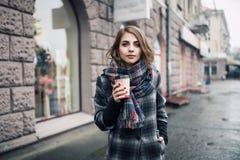 Hembra adulta joven con la taza de café de papel que permanece en la calle de la ciudad en día lluvioso nublado; Fotografía de archivo