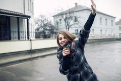 Hembra adulta joven con la taza de café de papel que permanece en la calle de la ciudad en día lluvioso y agitar nublados; Fotos de archivo