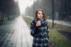 Hembra adulta joven con la taza de café de papel que permanece en parque de la ciudad en día lluvioso nublado; Fotos de archivo