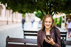 Hembra adulta joven sonriente atractiva que manda un SMS en el teléfono celular al aire libre en un banco Fotos de archivo libres de regalías