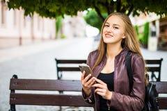 Hembra adulta joven sonriente atractiva que manda un SMS en el teléfono celular al aire libre en un banco Imagen de archivo