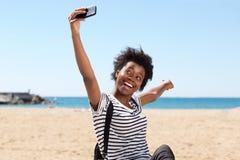 Hembra afroamericana joven sonriente en la playa y el selfie que habla Fotografía de archivo libre de regalías