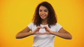 Hembra afroamericana sincera que hace el corazón con las manos, confesión del amor, sensaciones almacen de metraje de vídeo