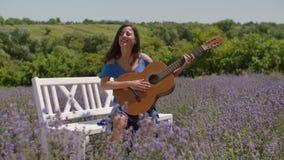 Hembra alegre con la guitarra que canta en campo de la lavanda almacen de metraje de vídeo