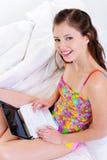 Hembra alegre feliz en cama con la computadora portátil Foto de archivo libre de regalías