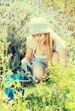 Hembra alegre que planta las flores en yarda Fotografía de archivo