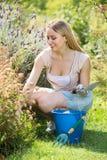 Hembra alegre que planta las flores en yarda Imagen de archivo libre de regalías